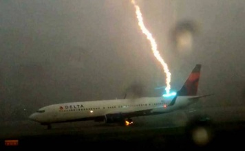 While filming the line of planes all piled up amid a ground hold in Atlanta on 8/18/15 because of heavy rain and thunderstorm, this guy happened to capture this direct lightning strike on a 737.