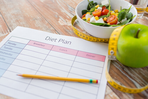 close-up-of-diet-plan-and-food-on-table