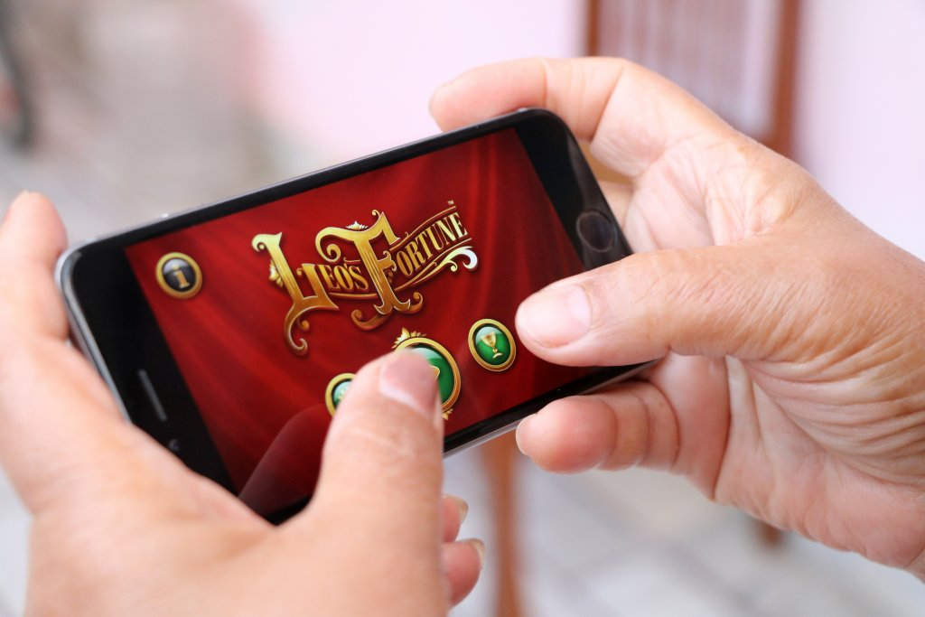 person-playing-app-on-mobile-phone